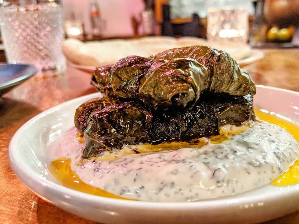 Stuffed grape leaves are piled on thick yogurt and olive oil on a small white plate on a copper bar top.