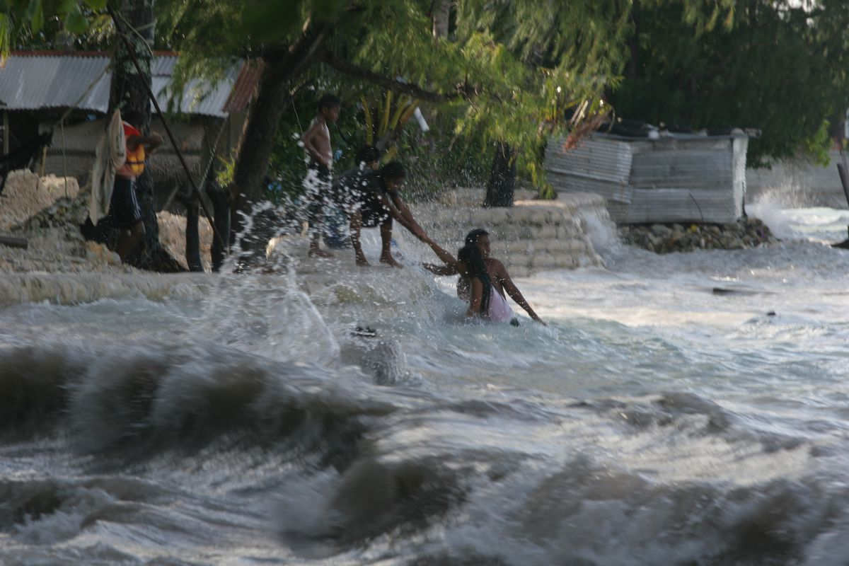 People rush to find safety and higher ground as floodwaters rush in and inundate a neighborhood.