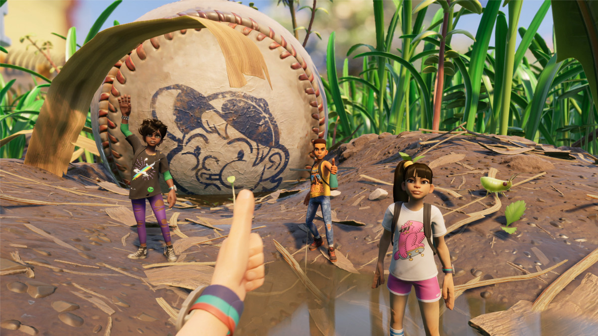 Three teens stand in front of a massive baseball. One gives a thumbsup to the other.