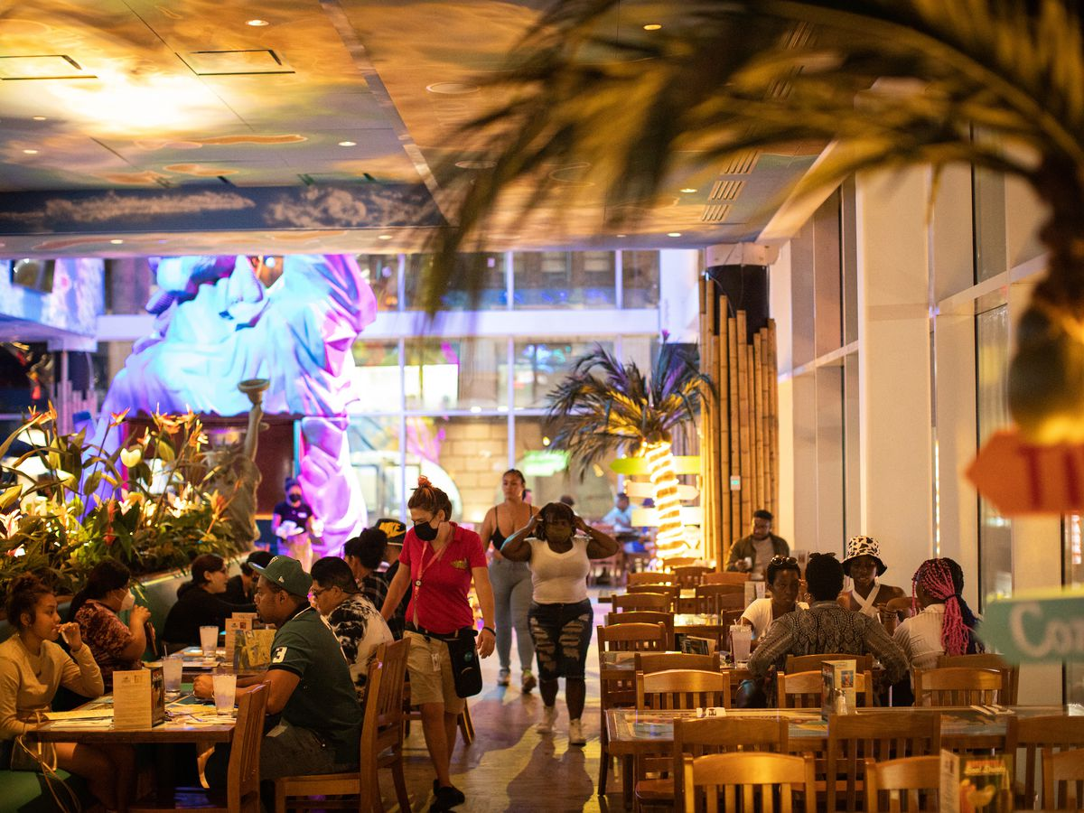 Tourists dine on wood tables in a tropical dining room.