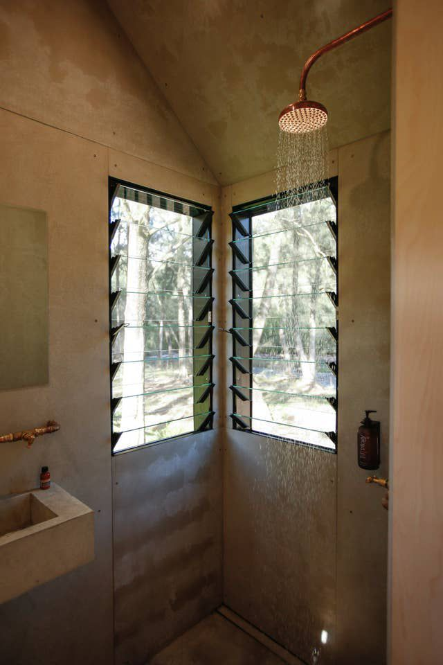 Compact shower in one corner of the tiny house featuring copper and brass fixtures and two rectangular windows.