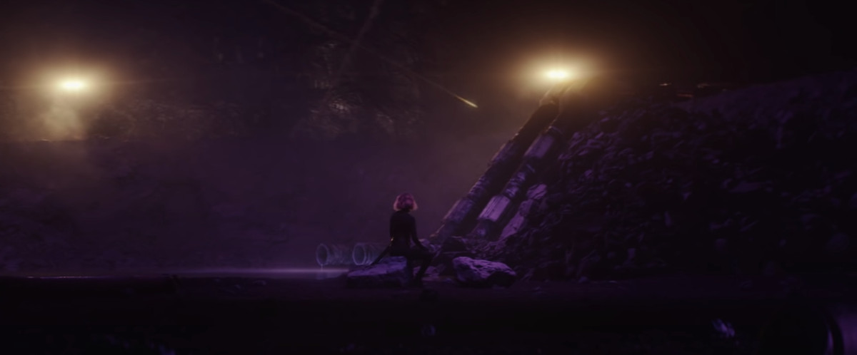 A figure who appears to be Black Widow sits on some rubble in an unearthly environment in Loki.