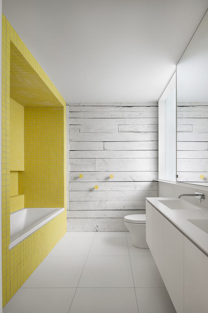 Yellow tile around the tub in a white bathroom.