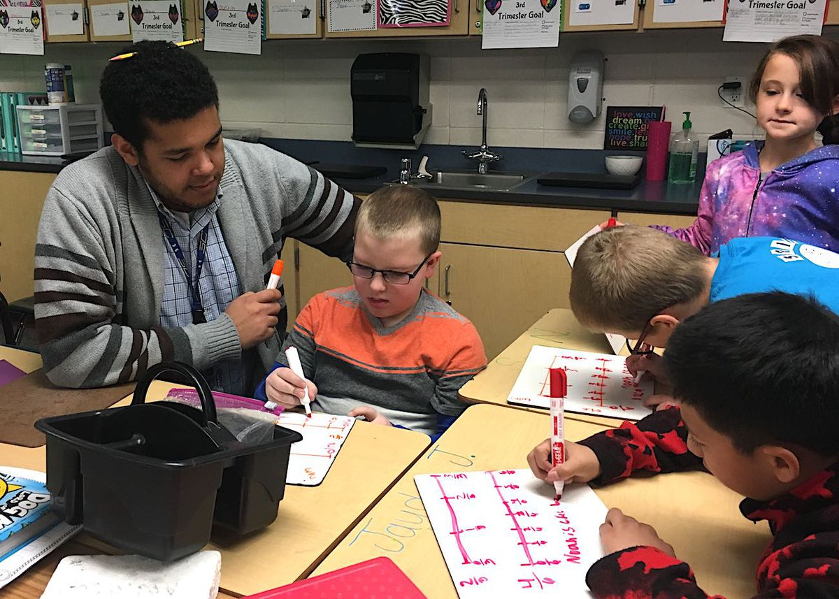 Jordan Dixon, a paraprofessional at Heiman Elementary, works with students during a math lesson.