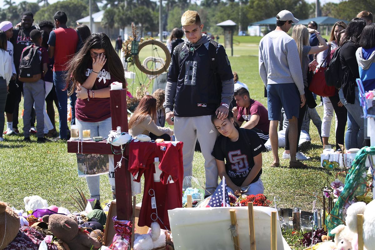 Students from Marjory Stoneman Douglas High School stand together at a memorial in March 2018 in Parkland, Florida.