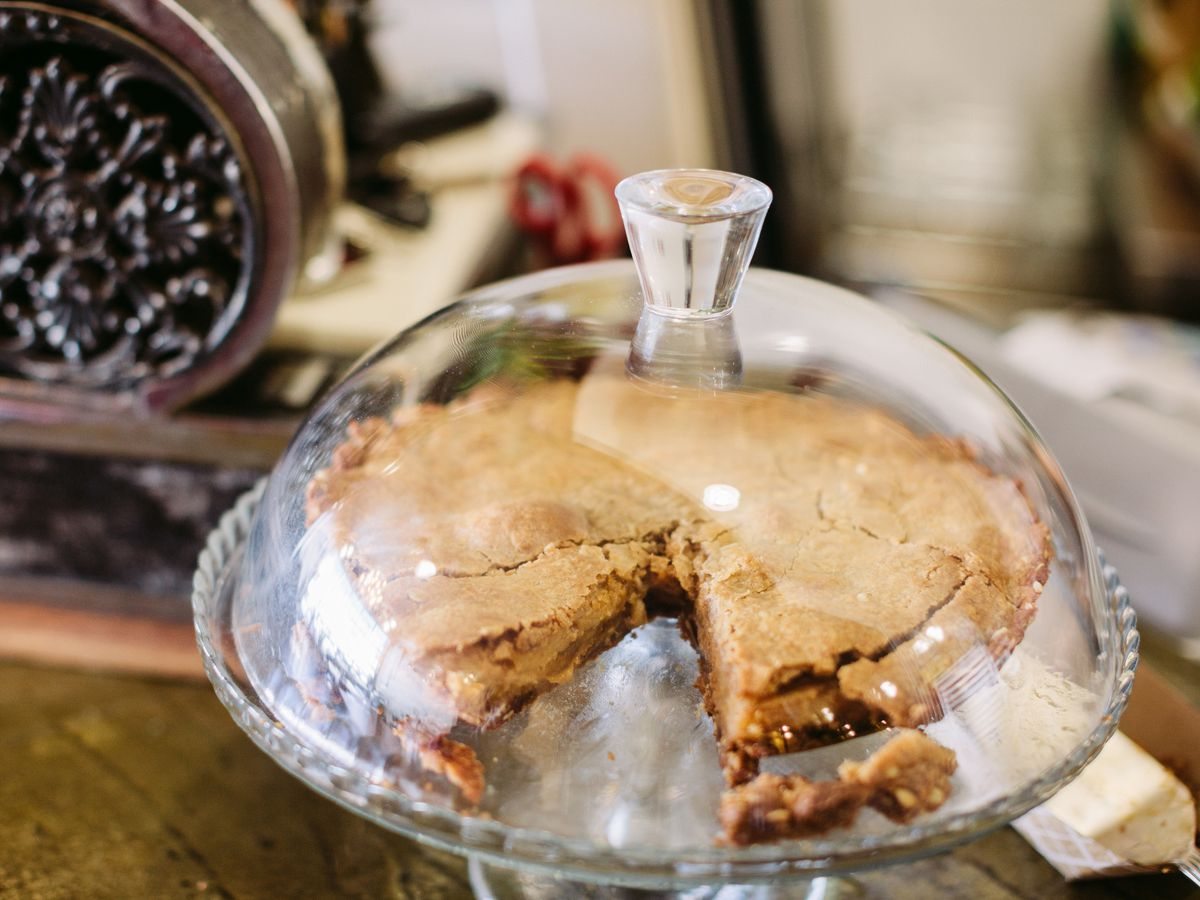 A pie in a glass pie pastry stand.