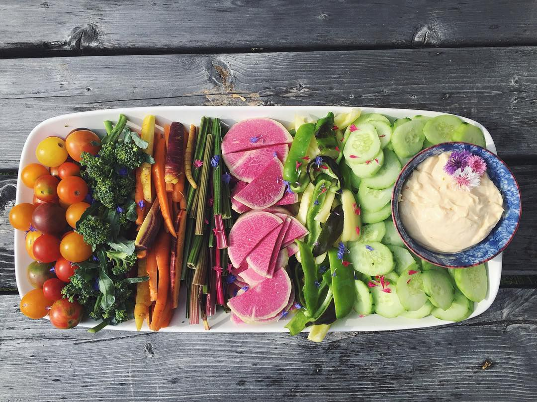 A tray of fresh vegetables and dip from Vermont's Farmers and Foragers. The tray sits on top of a wooden table.