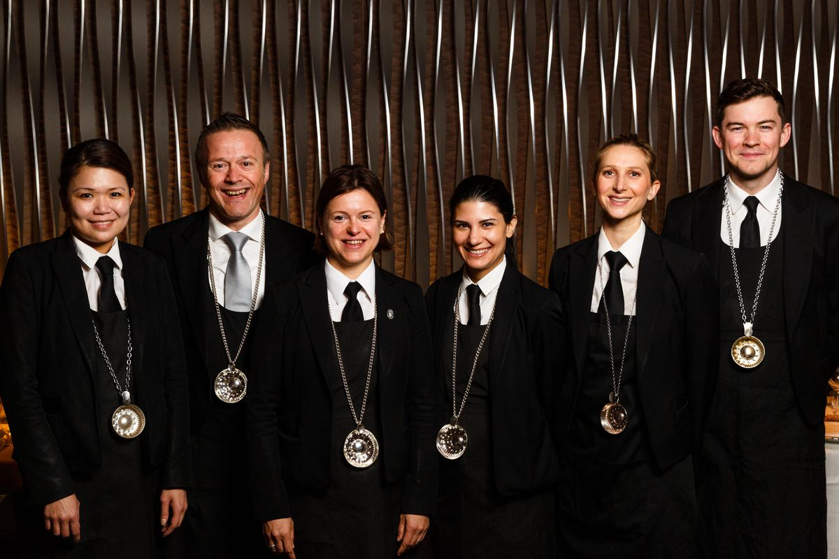 Beverage director Aldo Sohm (second to left) stands with his team of suited sommeliers, each of whom carriers a silver tastevin hanging around their neck