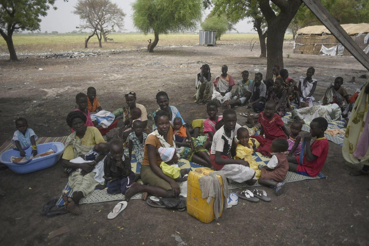 In the photo of  March 4, 2015, mothers sit with their children waiting to receive malnutrition assistance in the Nile west bank village of Lul South Sudan's Upper Nile state. The South Sudanese government has stopped operations of two newspapers, editors
