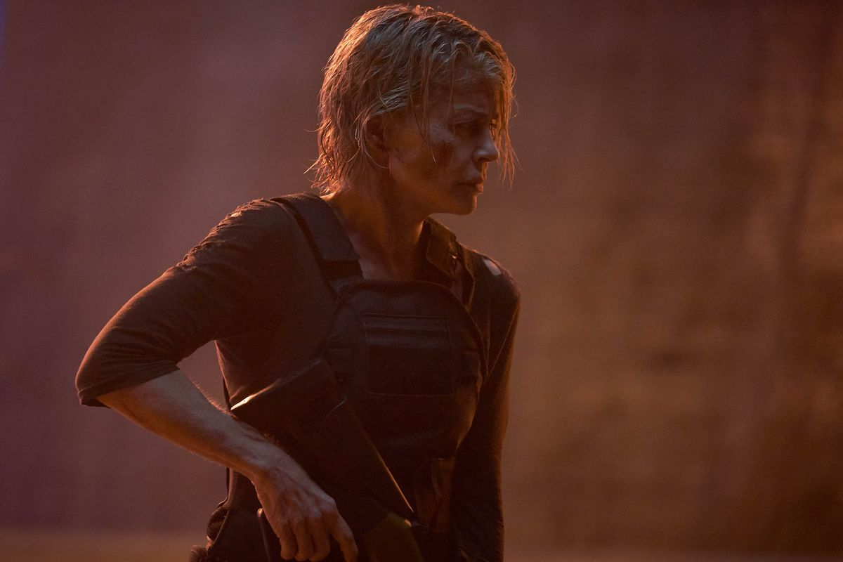 sarah connor roughed up holds her assault rifle in a bath of red light