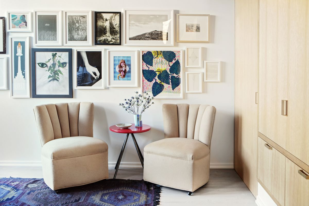 A corner of a bedroom. There are two arm chairs with a red table that holds a vase with flowers. There are multiple framed works of art hanging on the white wall. Against the other wall is a wall of wooden storage cabinets. There is a multi-colored patter