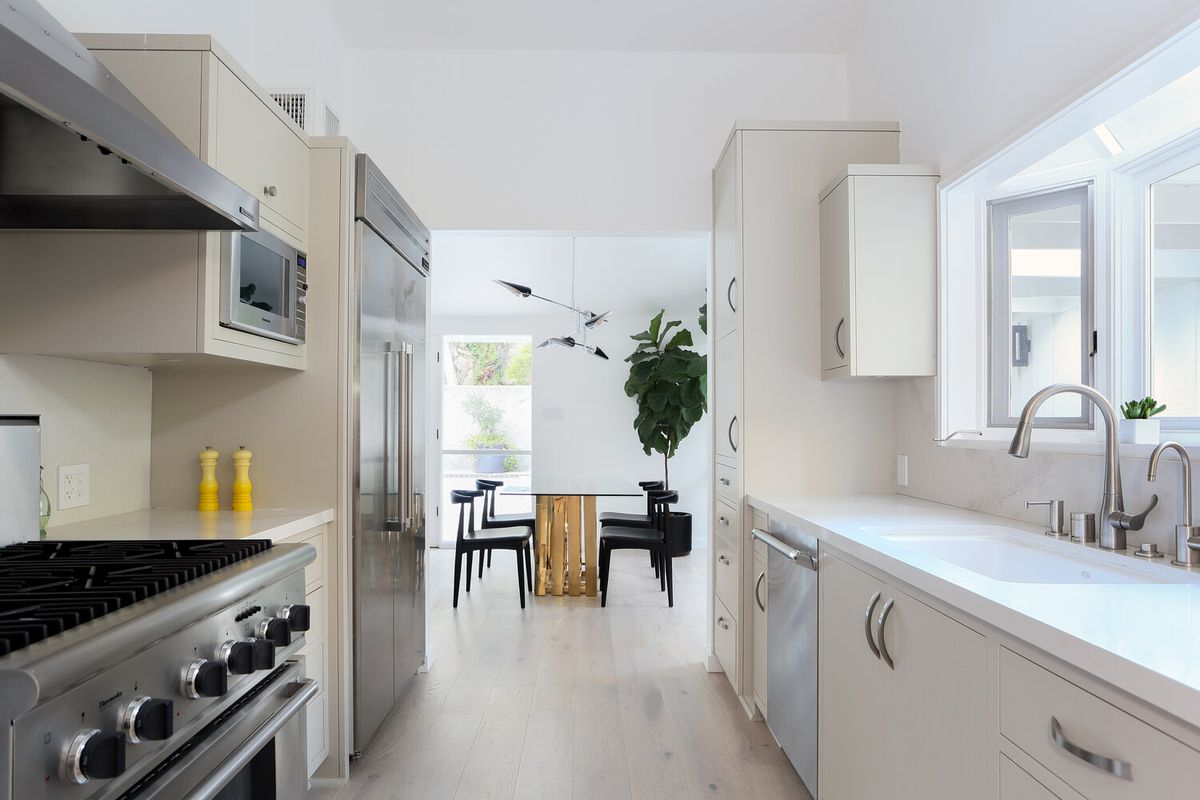 a photo of a galley-style kitchen with updated counters and stainless steel appliances.