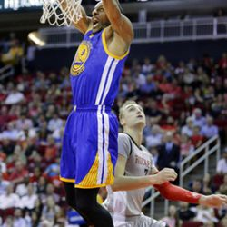 Golden State Warriors' Andre Iguodala (9) dunks over Houston Rockets' Sam Dekker (7) in the first half of an NBA basketball game in Houston, Tuesday, March 28, 2017. (AP Photo/Michael Wyke)