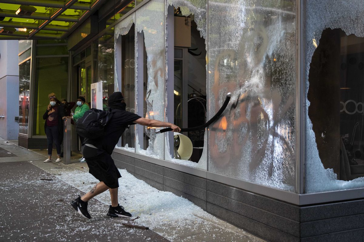 A protester breaks a storefront window near State and Lake in the Loop as thousands in Chicago joined national outrage over the killing of George Floyd in Minneapolis police custody, Saturday afternoon, May 30, 2020.