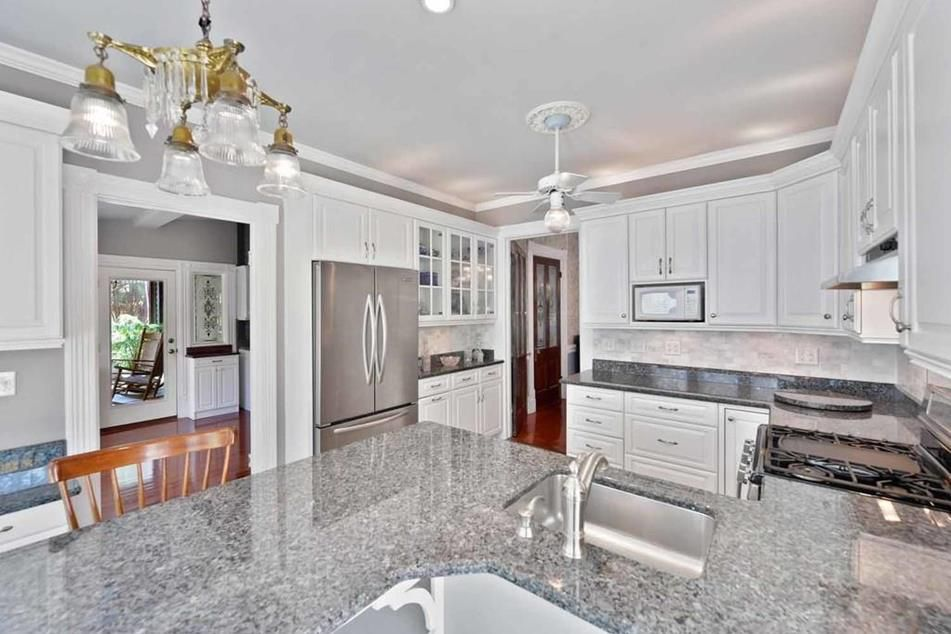 Kitchen with a ceiling fan and chandelier that contrasts so much white.