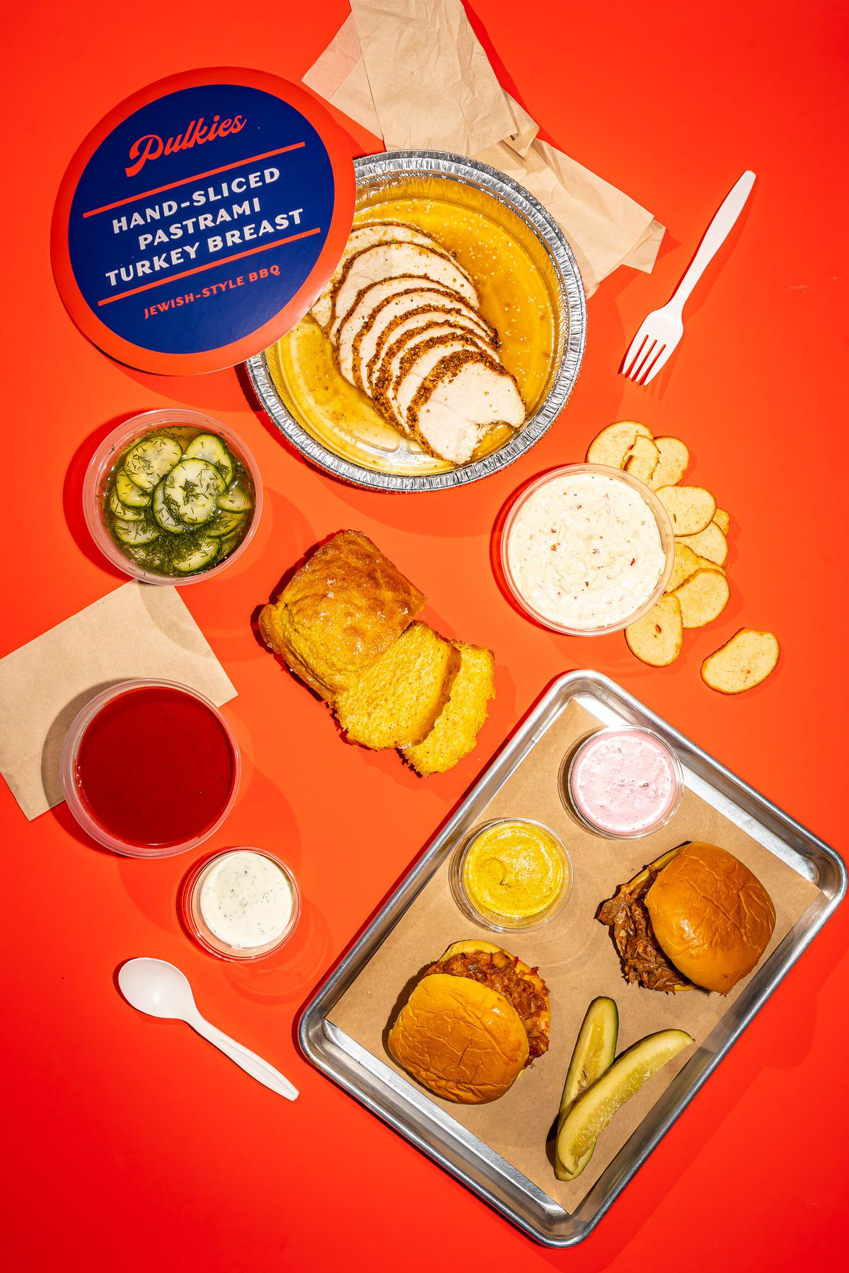 An overhead photograph of a spread of foods, including two pulled turkey sandwiches, plastic to-go containers of dips, sliced breads, pickles, and plastic utensils