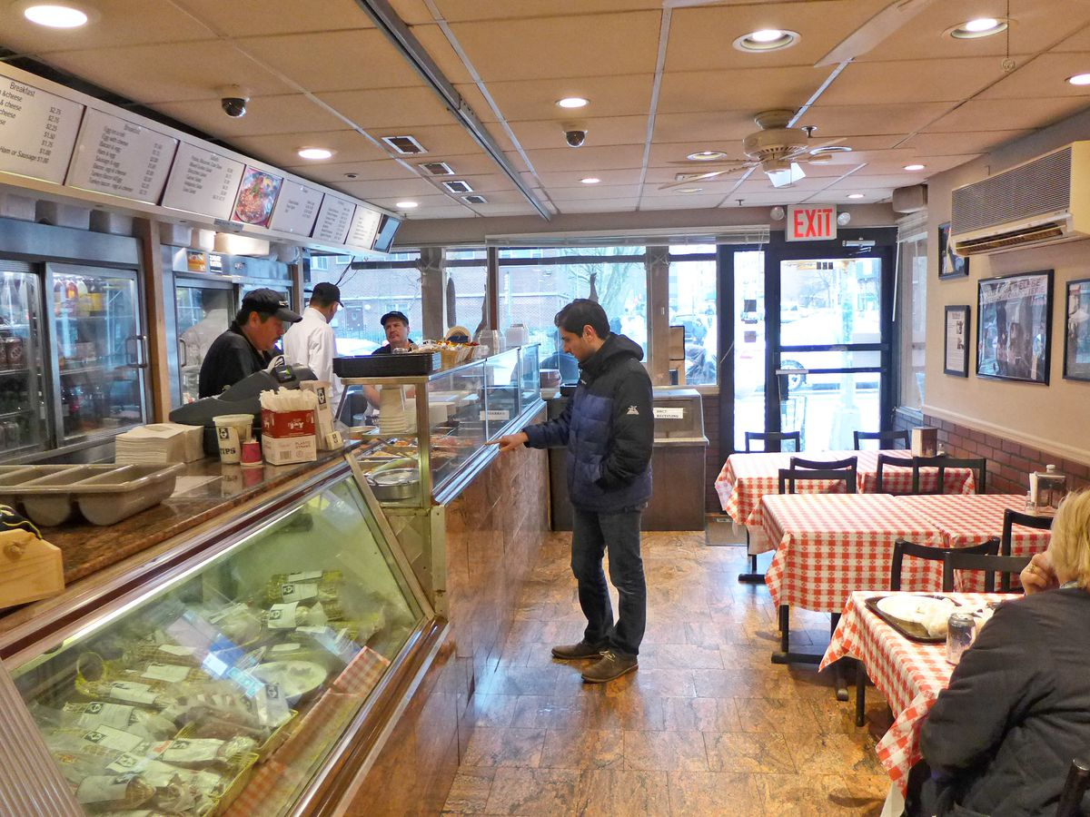 An Italian deli interior with red checked tablecloths and guys standing behind a counter with glass cases.