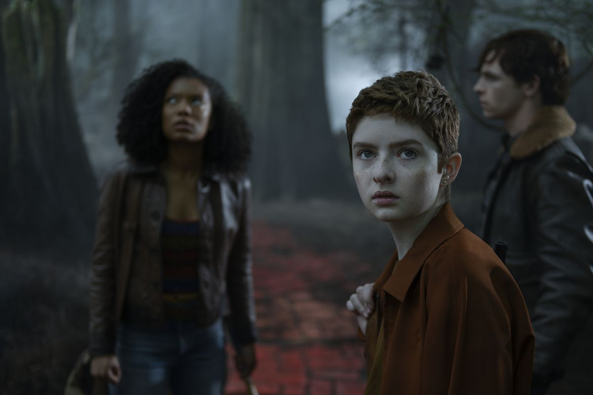 Three of Sabrina's friends stand uneasily in a dark blue-green wood, on a dark red stone path.