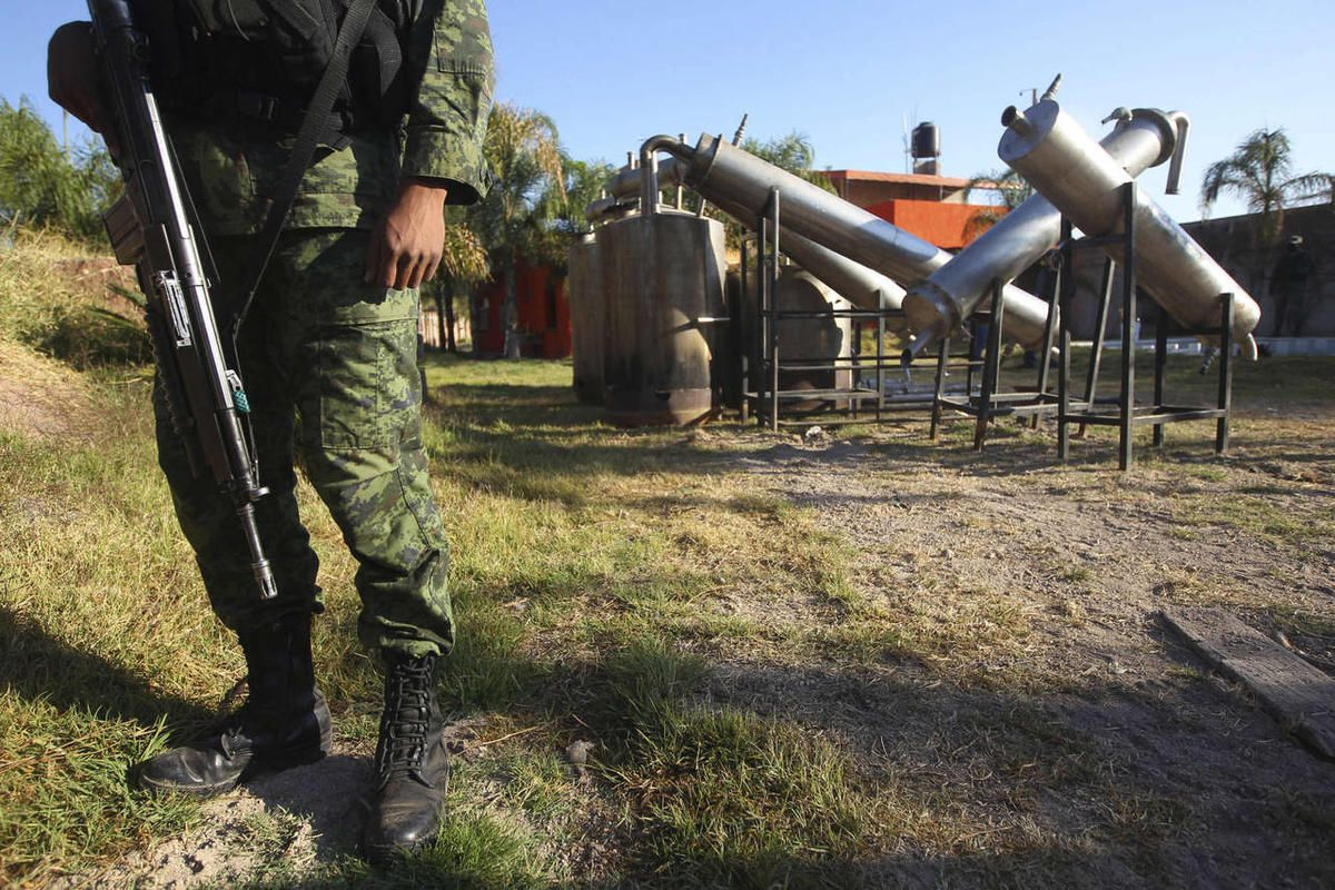 """A soldier stands in what was identified as \""""metal reactors\"""" after a seizure of a large clandestine methamphetamine lab at a ranch in Tlajomulco de Zuniga, on the outskirts of Guadalajara, Mexico, Thursday Feb. 9, 2012."""