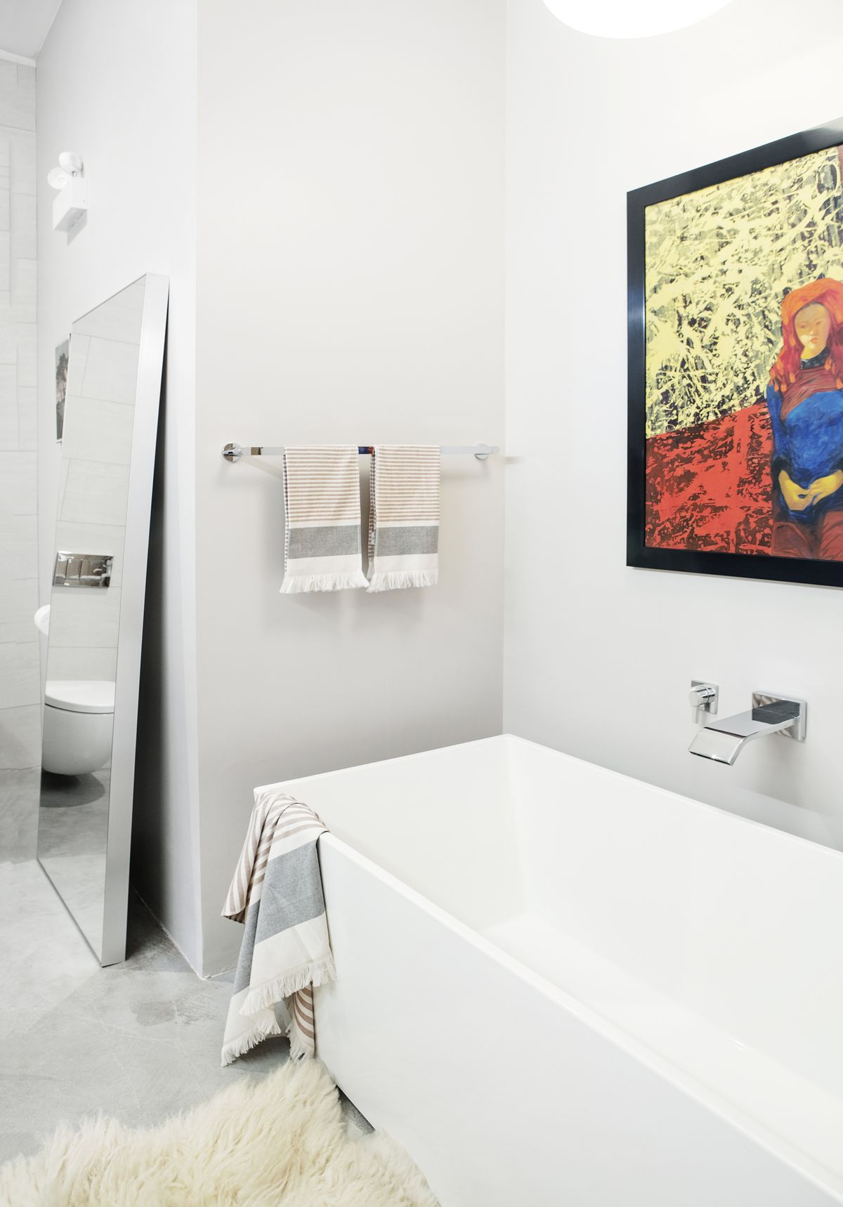 A bathroom. There is a white bathtub. Above the bathtub is a colorful work of art. There is a free standing mirror leaning against one of the walls. The walls are painted white.