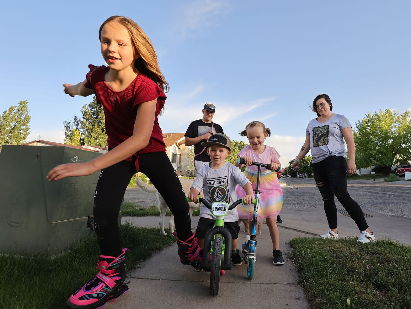 Tyler and Stephanie Parkin walk and bike with their three kids near their home in Roy, Utah, in May 2021.