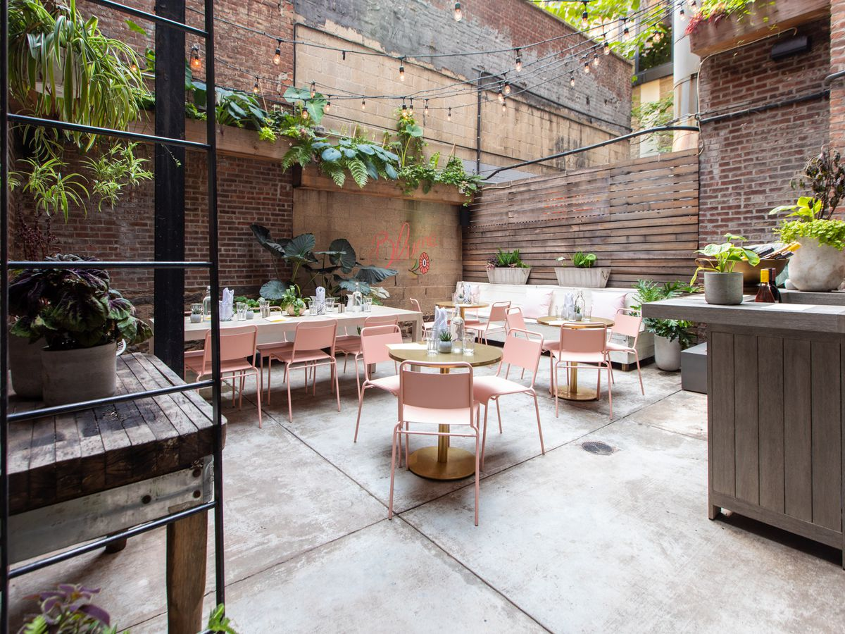 A restaurant backyard with several tables and chairs placed in a courtyard with a red brick wall