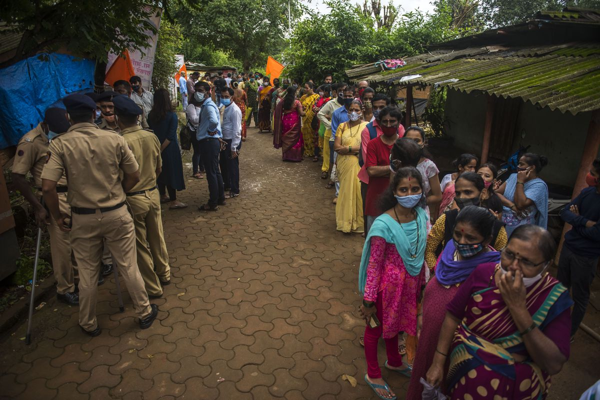 People stand in a line outside a vaccination clinic in India.