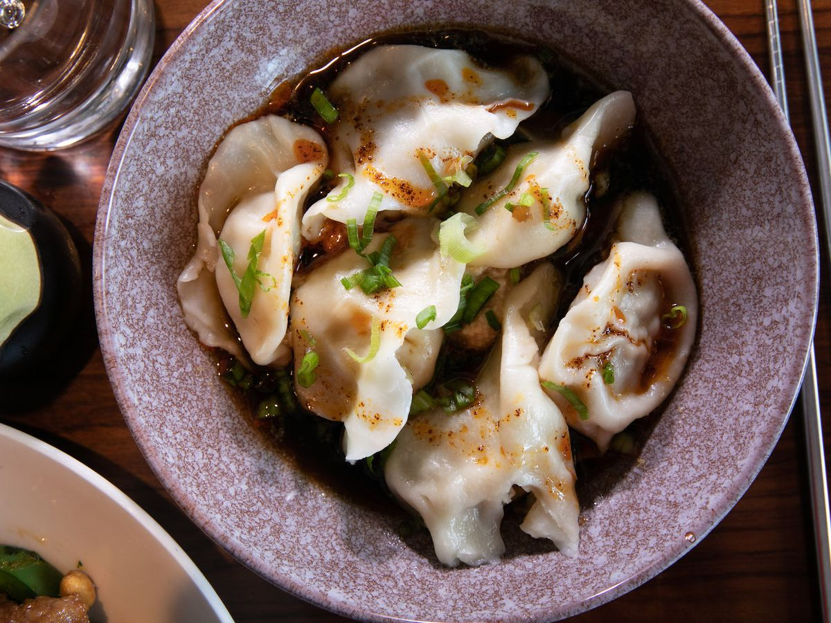 Dumplings topped with delicate chives and a slick chili broth