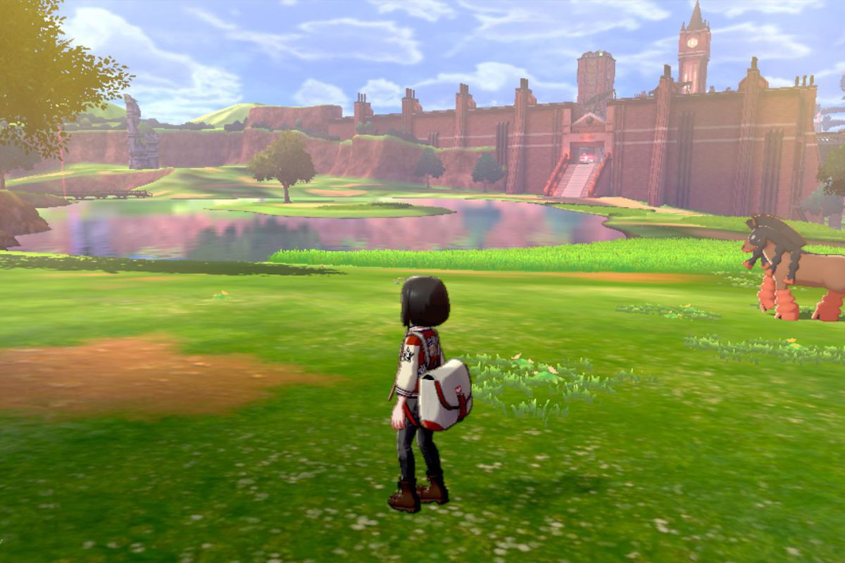 A Pokémon trainer stands in the Wild Area with a Mudsdale roaming in the background