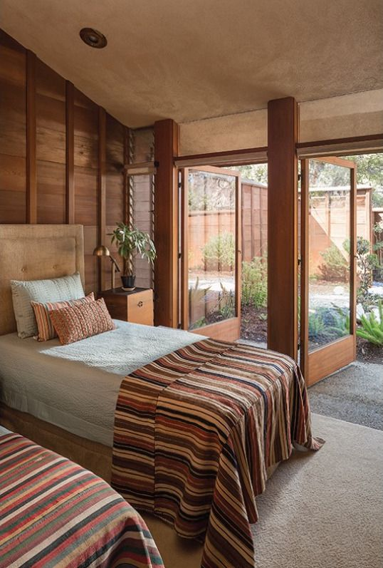 Interior shot of a bedroom with high walls paneled in redwood and glass doors opening to a private patio.