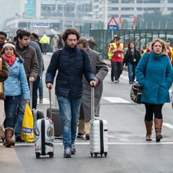 People walk away from Brussels airport after explosions rocked the facility in Brussels, Belgium Tuesday March 22, 2016.  Explosions rocked the Brussels airport and the subway system Tuesday, just days after the main suspect in the November Paris attacks was arrested in the city, police said.