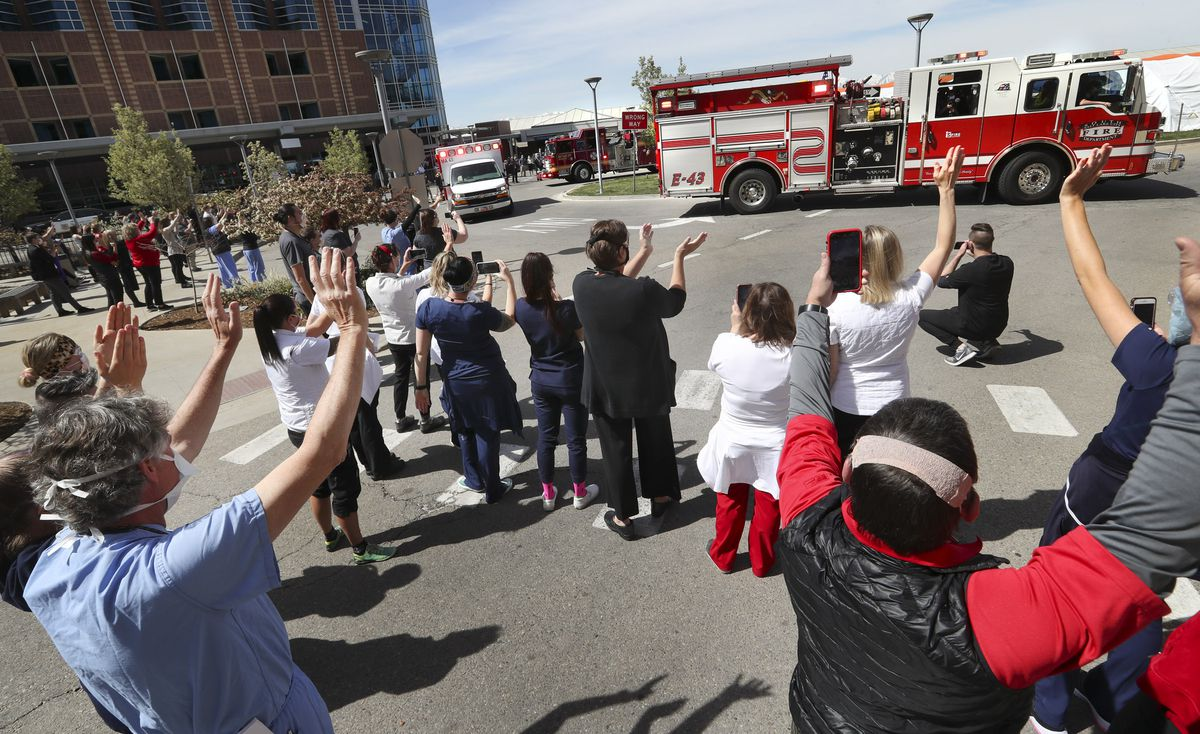 University of Utah Hospital staff clap and wave as firetrucks circle through the entrance of the Salt Lake City hospital during a first responder vehicle parade to honor health care workers on the front line of the coronavirus pandemic aon Monday, April 27, 2020. Firetrucks, ambulances and police vehicles flashed emergency lights and sounded their sirens as they drove past the hospital.
