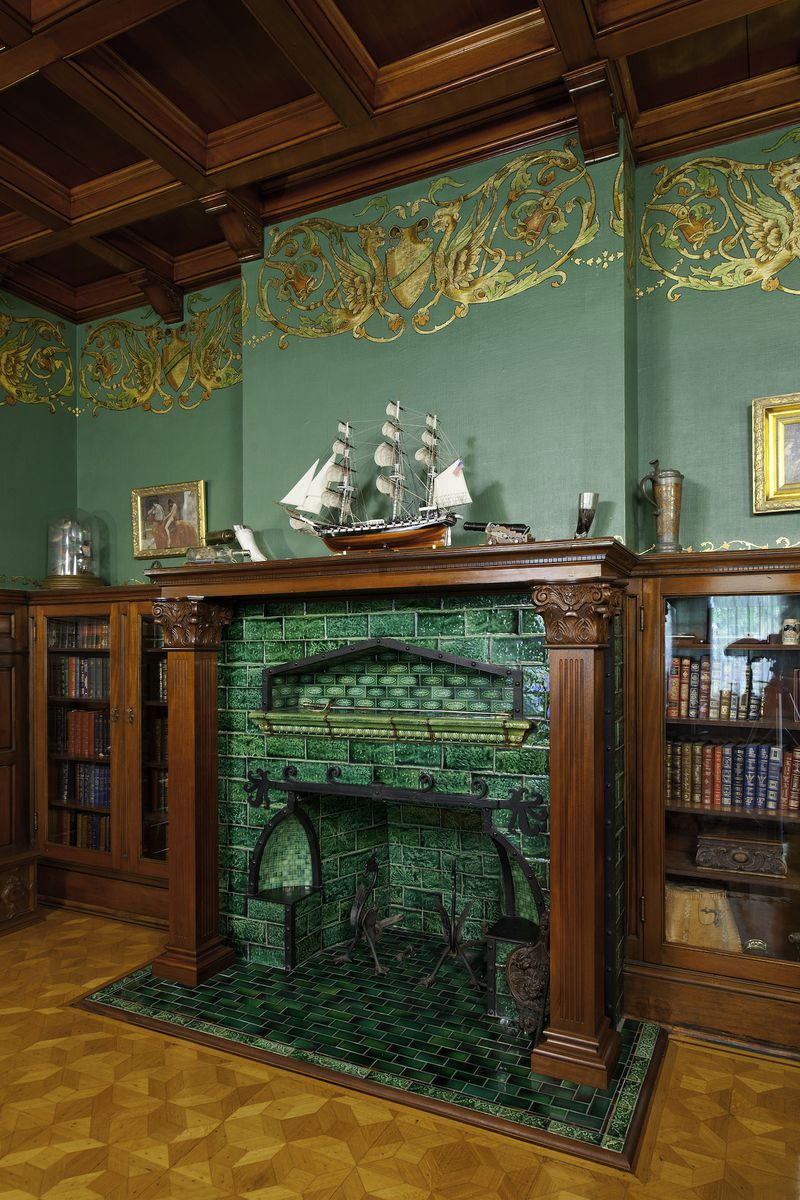 A rich royal green fireplace has tile, wood trim, and a ship on the mantle.