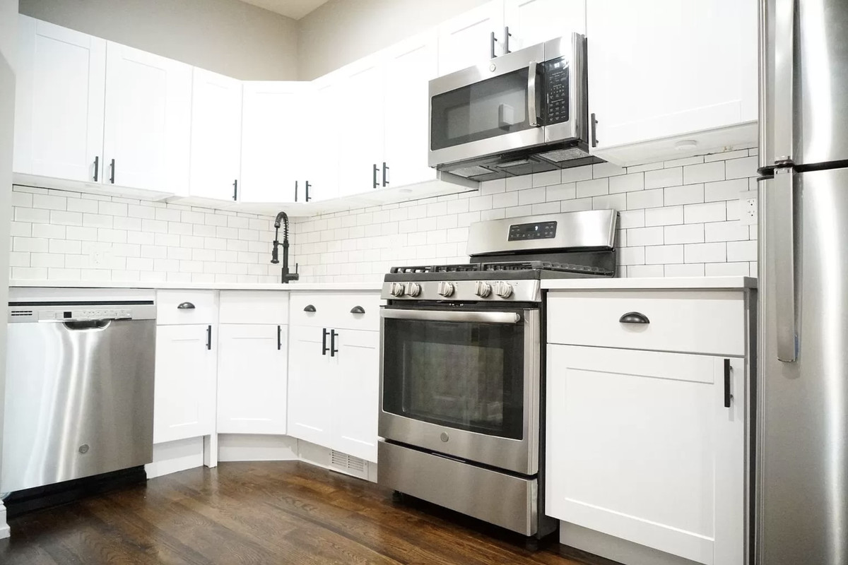 A view of the kitchen with white cabinets, black hardware, and silver appliances.