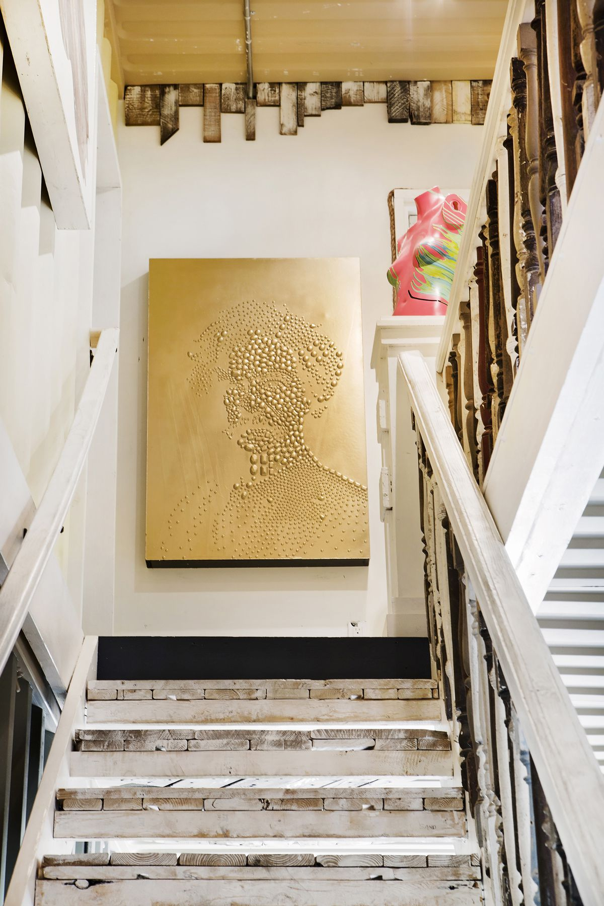 In the living room, two large black-and-white artworks show a female and male figures; random pieces of wood panel the basement, and it's all painted white; a long staircase has mismatched, salvaged balusters in the railing, and an abstract portrait of Ma