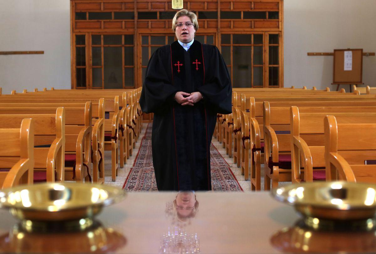 The Rev. Rola Sleiman wears a baby blue clerical shirt beneath a black robe.
