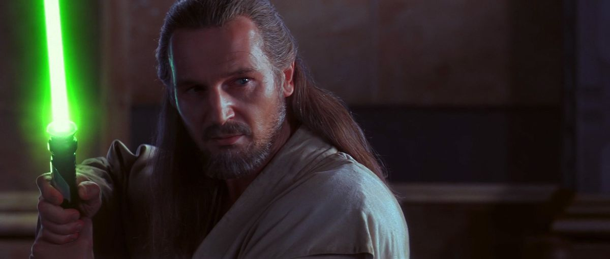 qui gon jinn holds up his lightsaber come his face in phantom threat
