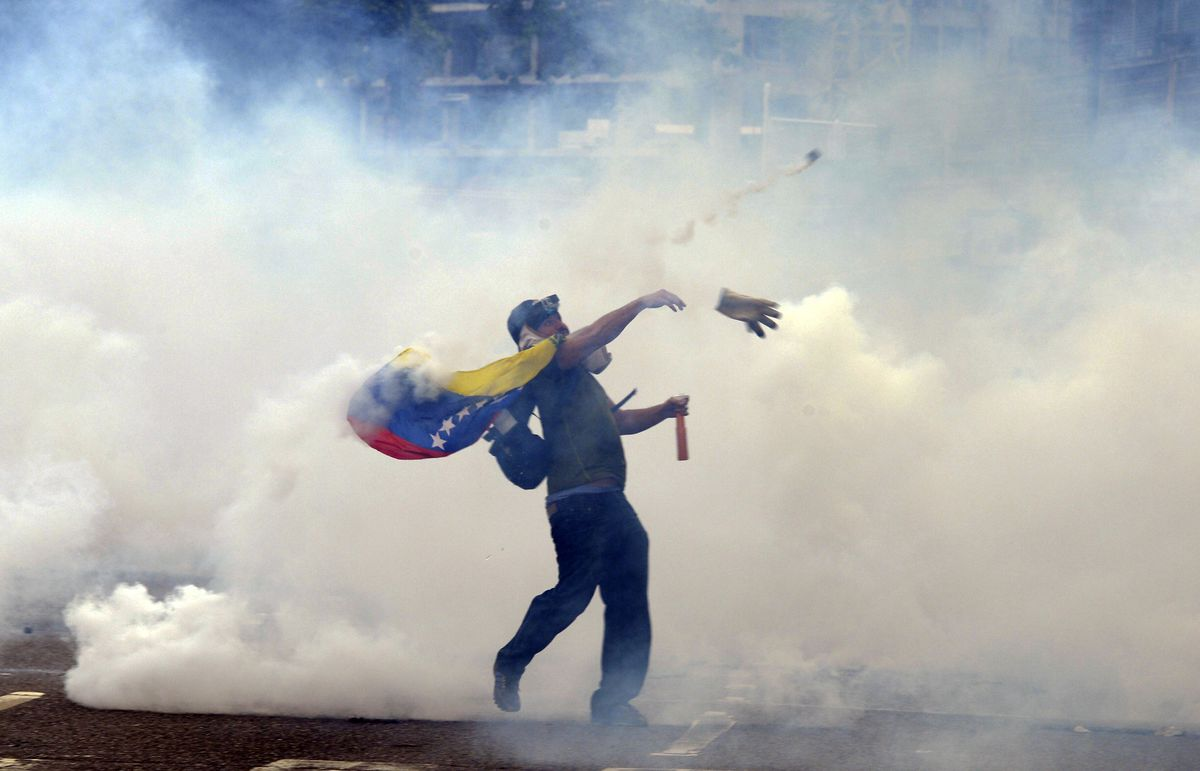A protester in Venezuela throws a stone at police.