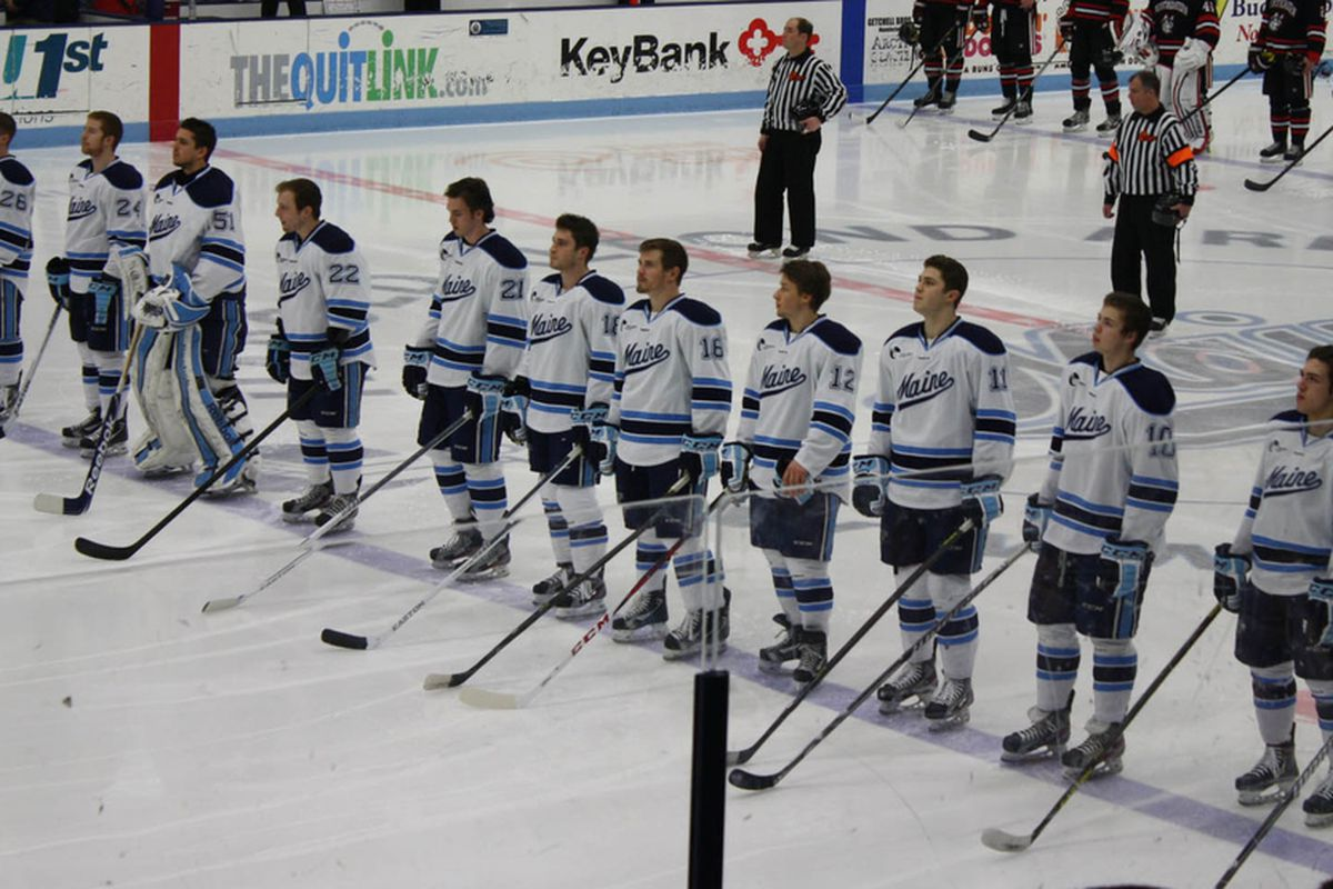 Kyle Beattie (21) lines up with fellow Black Bears for the national anthem on senior night in Orono, Maine.
