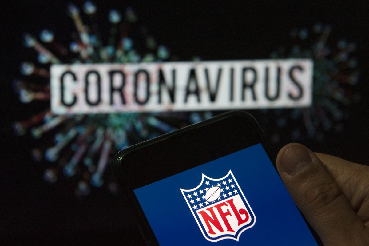 In this photo illustration the American football league The National Football League (NFL) logo seen displayed on a smartphone with a computer model of the COVID-19 coronavirus on the background.