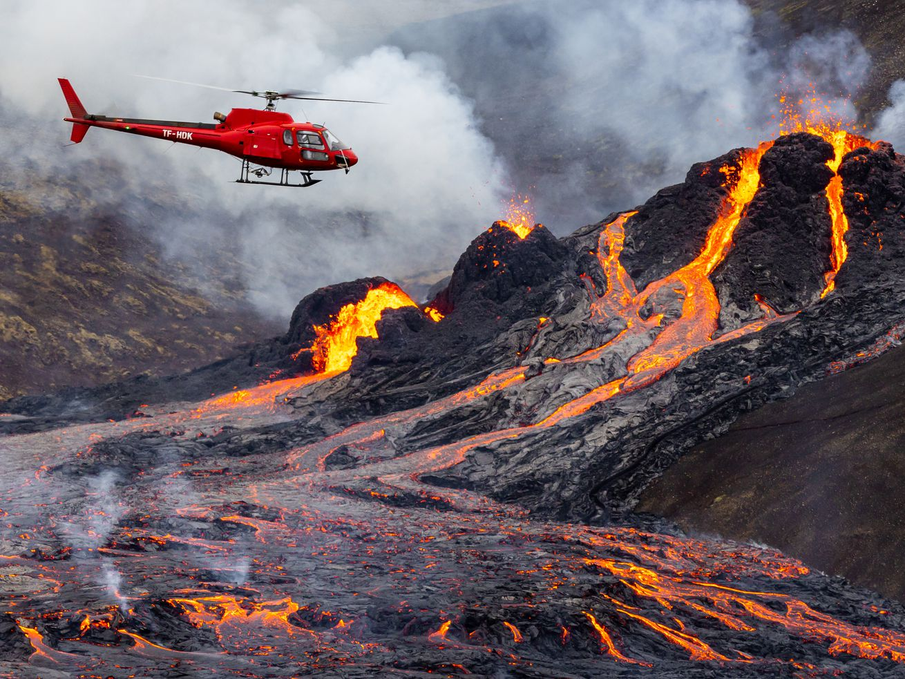 Streams of orange-red lava drip down the sides of a black mountain spewing plumes of thick, white smoke. A red helicopter hovers a little ways above the scene.
