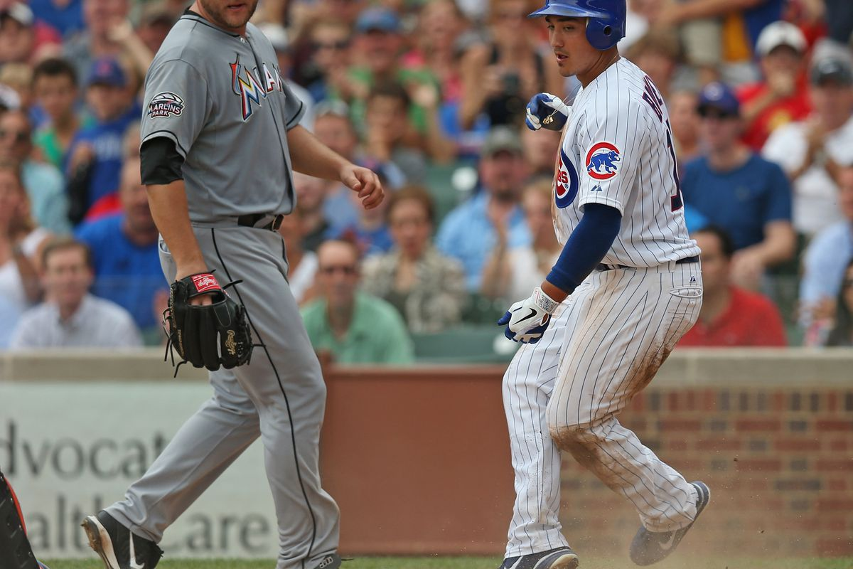 Darwin Barney of the Chicago Cubs scores a run as Mark Buehrle of the Miami Marlins backs up the plate at Wrigley Field in Chicago, Illinois. (Photo by Jonathan Daniel/Getty Images)
