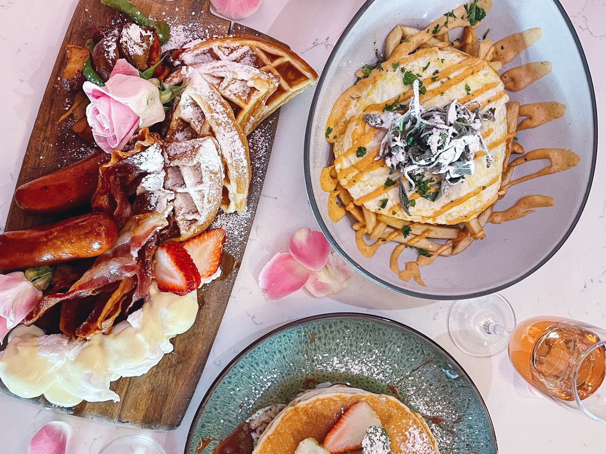 A dish with waffles, another with eggs, another with pancakes.