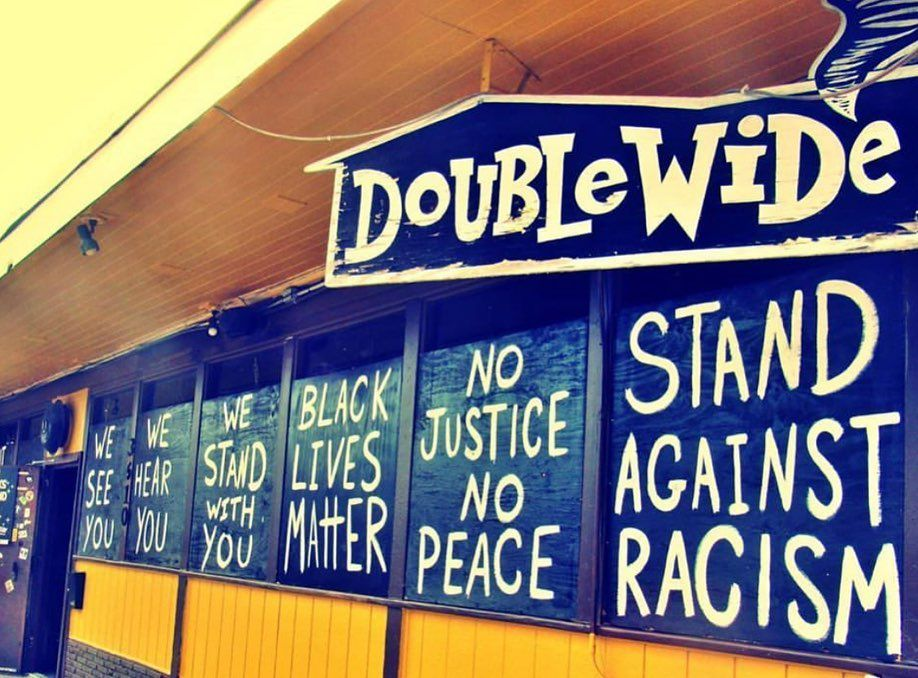 Blue-painted boards over restaurant windows painted with messages in support of Black Lives Matter protests.