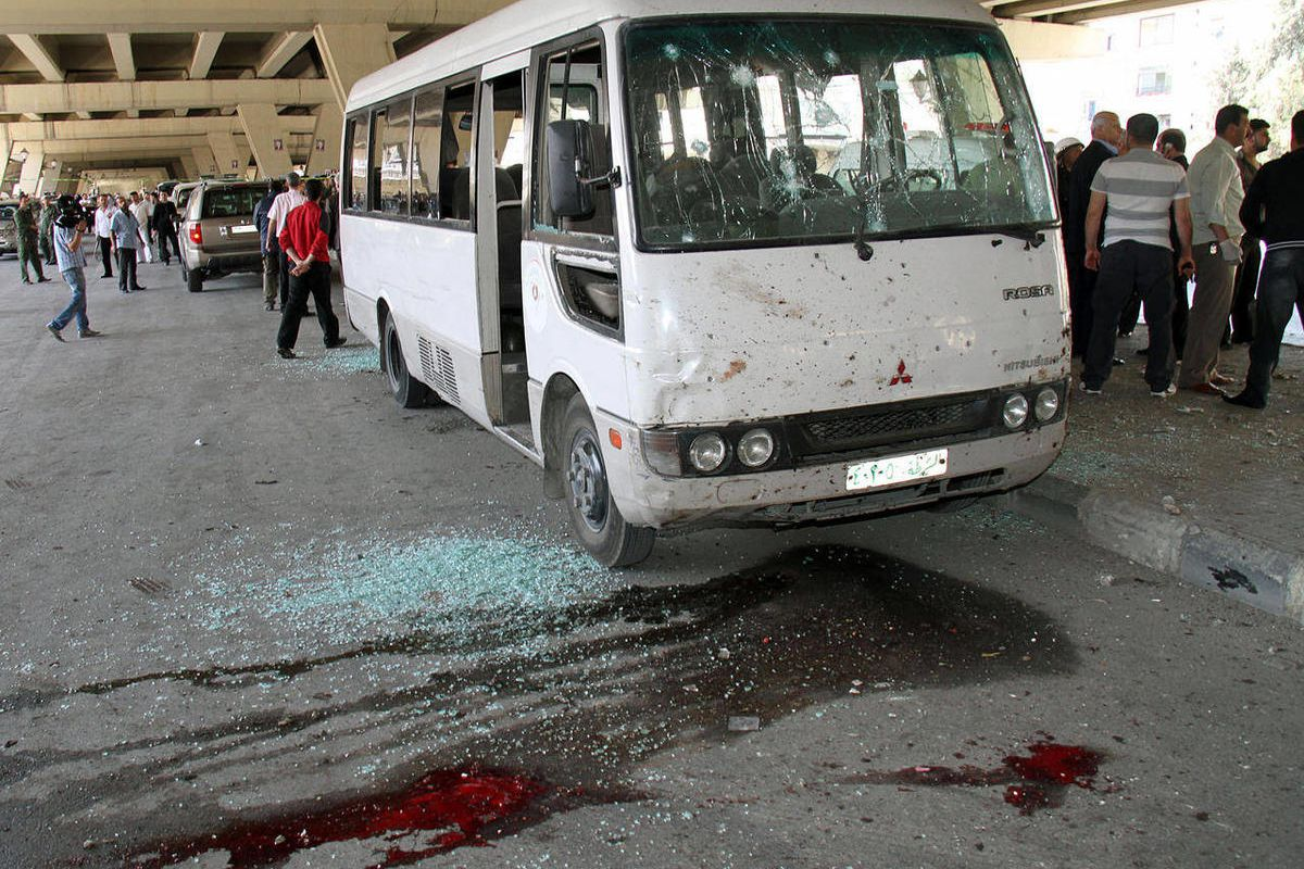 Syrian investigators, right, gather next to a damaged police bus that was attacked by an explosion in the Midan neighborhood of Damascus, Syria, on Friday April 27, 2012. A suicide bomber blew himself up across the street from a mosque in the Syrian capit