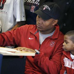 Heritage Hall's Barry J. Sanders signs a letter of intent to attend Stanford as his brother Terrance Johnson, 4, looks on during national signing day at Heritage Hall in Oklahoma City, Wednesday, Feb. 1, 2012.