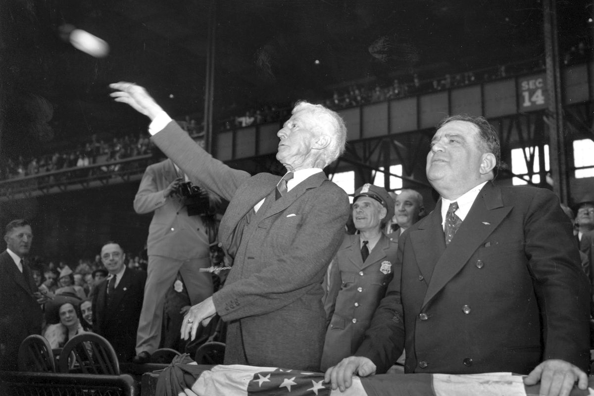 Baseball commissioner Kenesaw Mountain Landis, left, throws out the first pitch at the 1941 World Series.