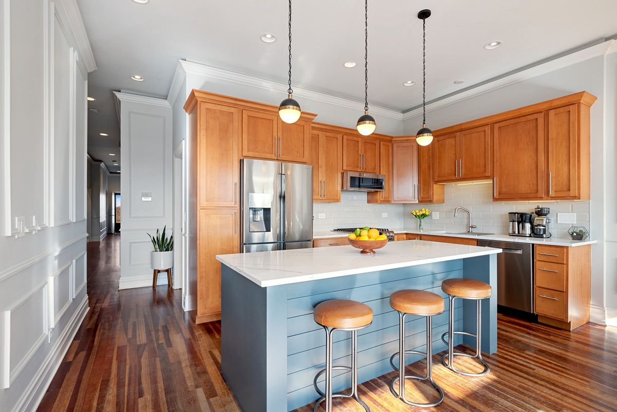 A kitchen with a large rectangular island, three stools, and wooden cabinets.