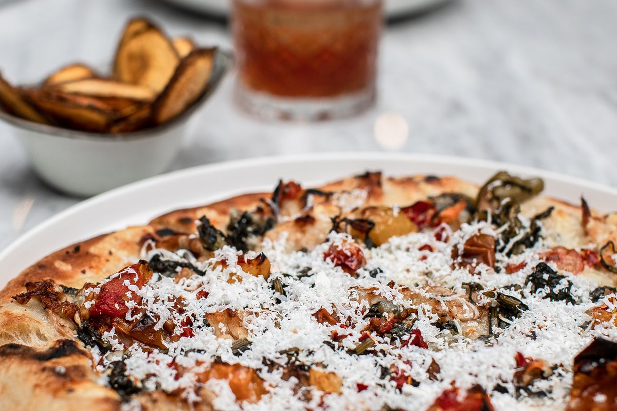 A barbecue-topped pizza with charred crust served on a white plate