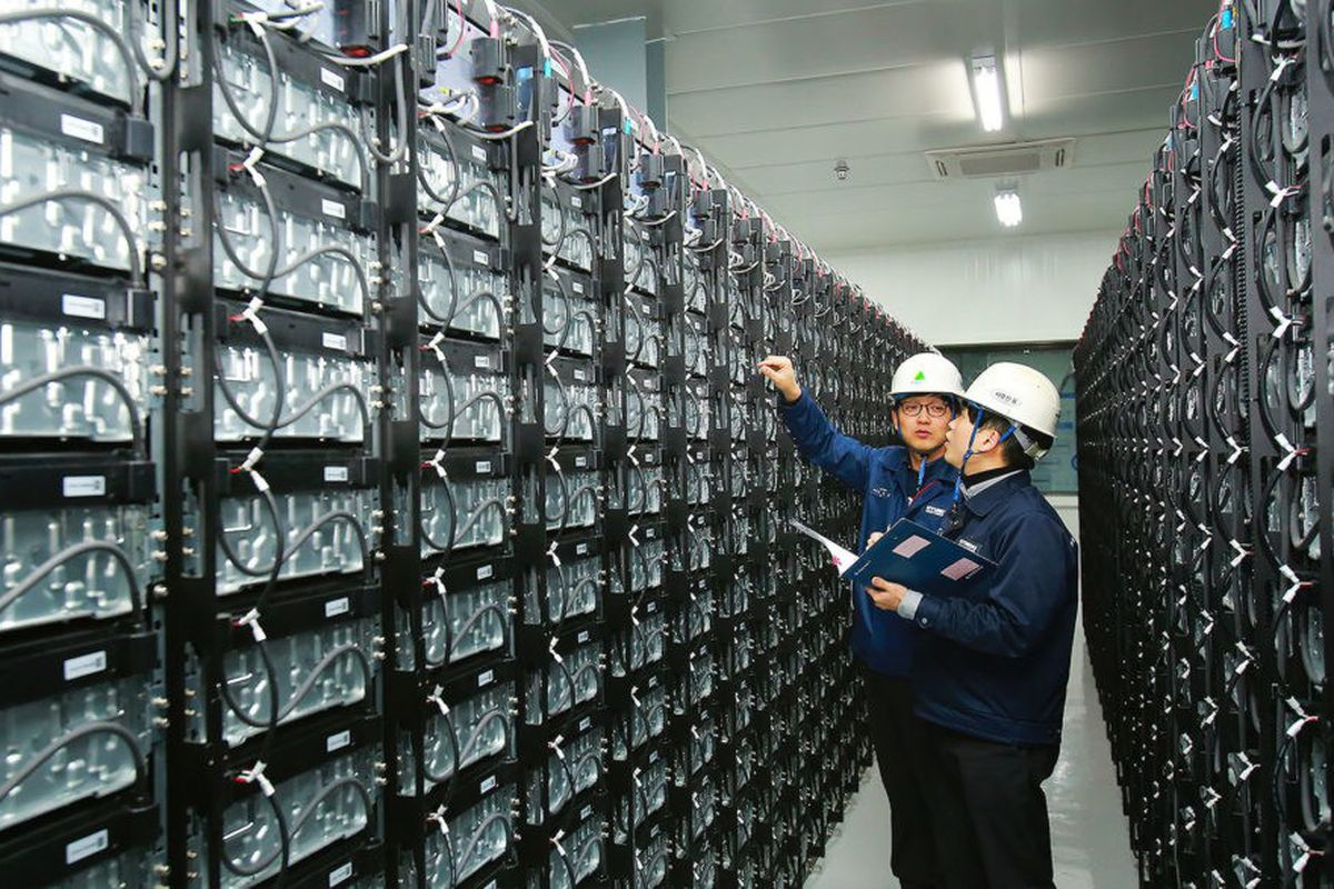 Photo of two men in hard hats examining a wall of wires.
